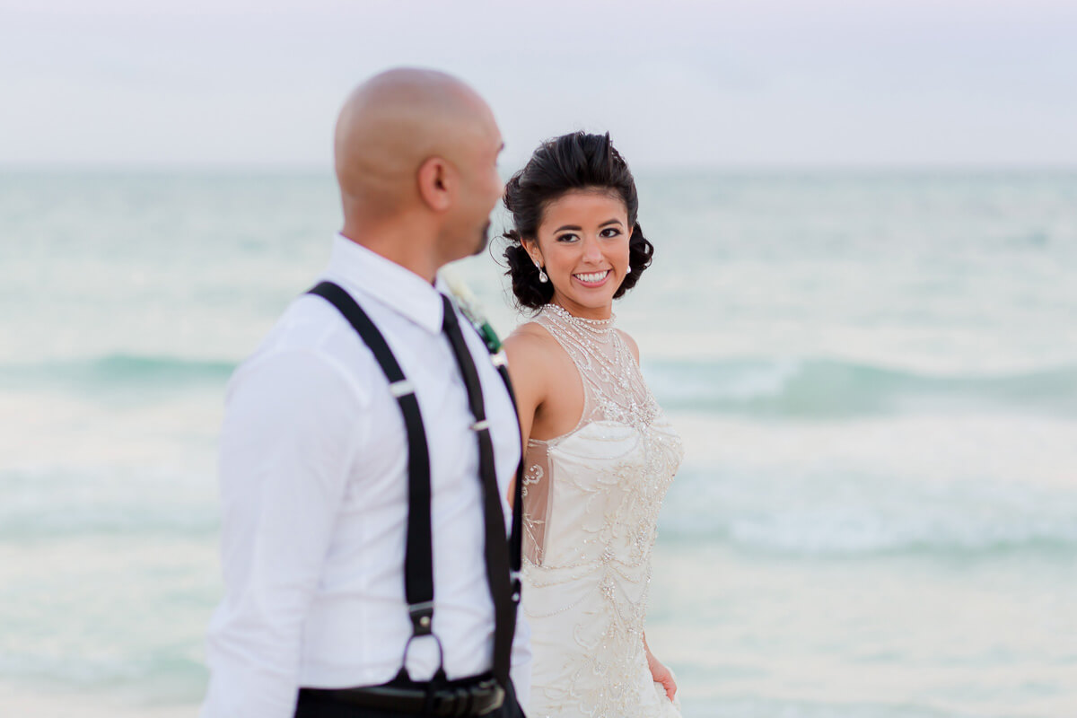 Bride and groom walking on beach at Secrets Maroma