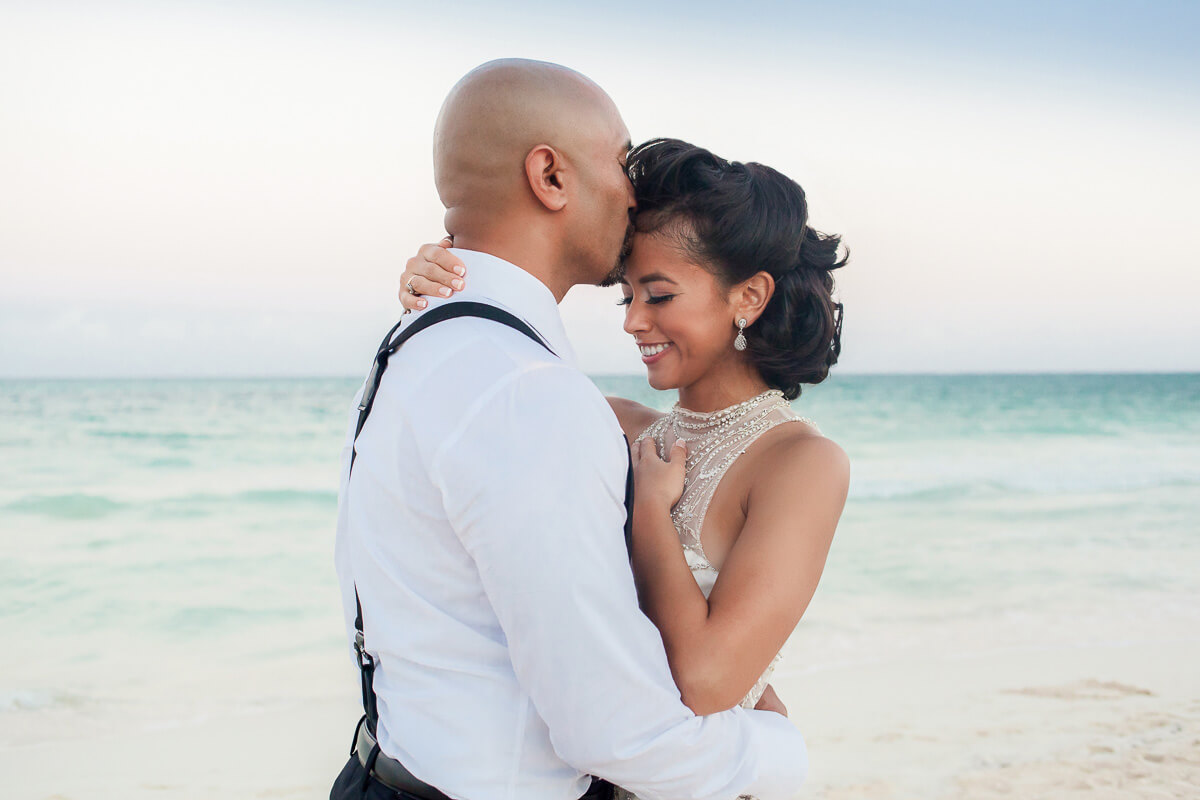 Groom kissing bride on beach at Secrets Maroma