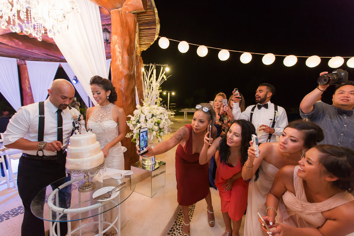 Guests watching cake cutting at Secrets Maroma