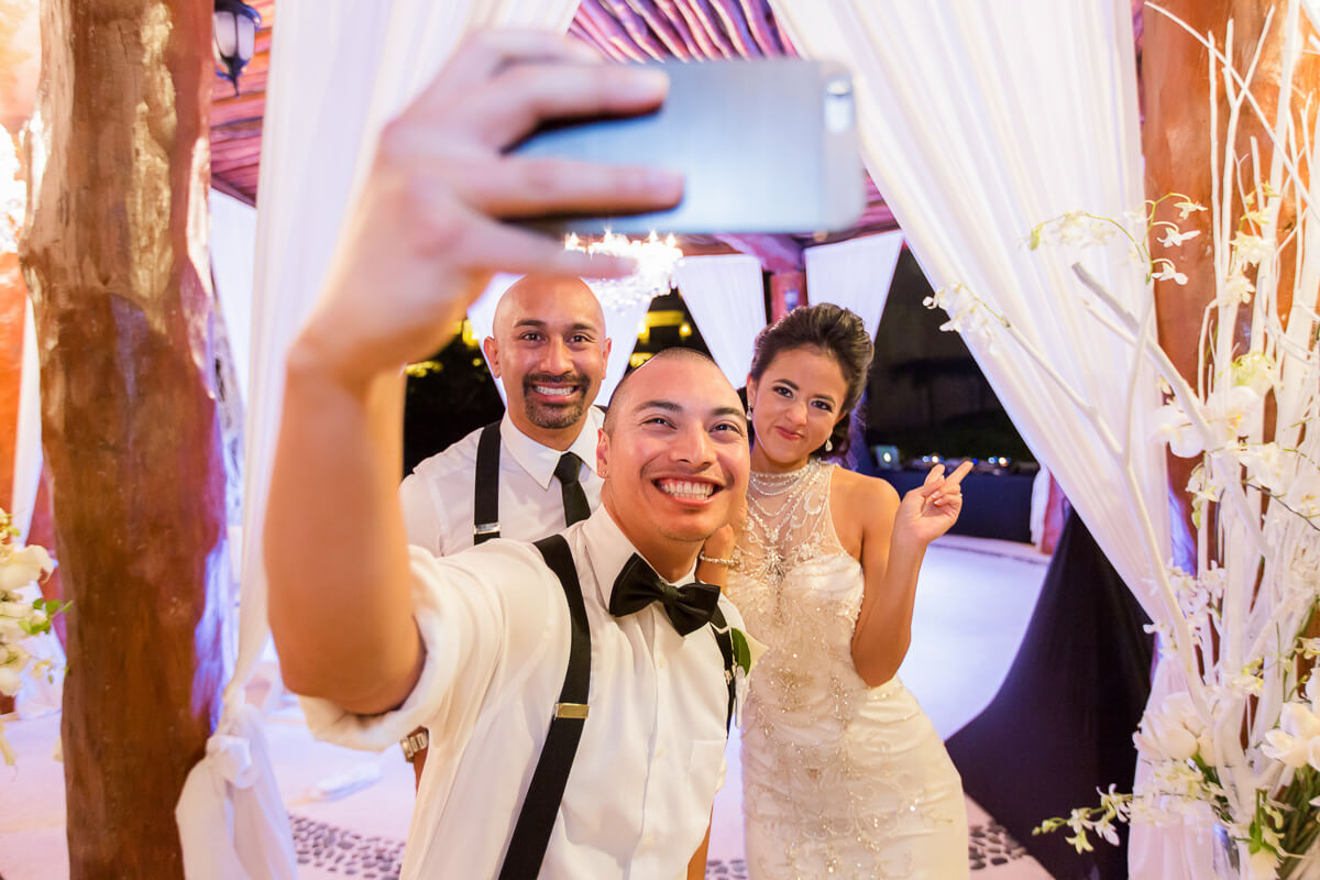 Groomsman taking selfie with bride and groom at wedding reception