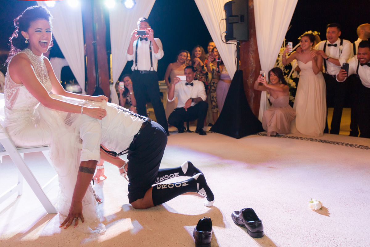 Broom taking off garter at wedding.