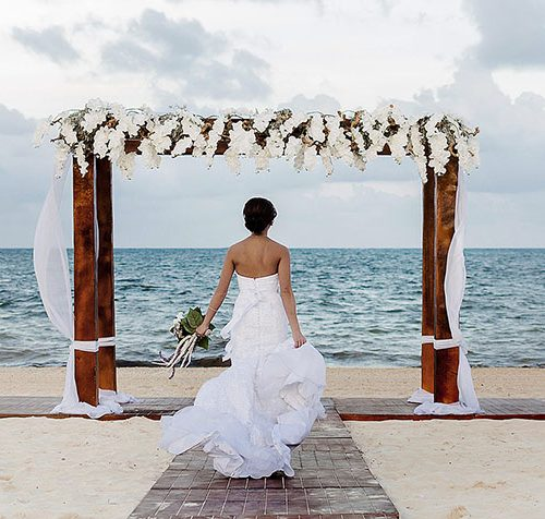Bride running on beach in Cancun