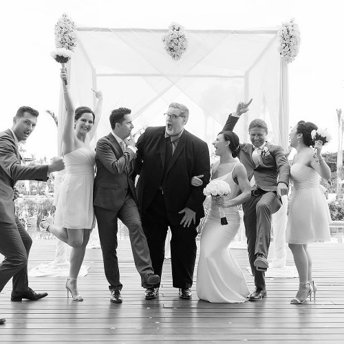 Bridal party with minister having fun after wedding