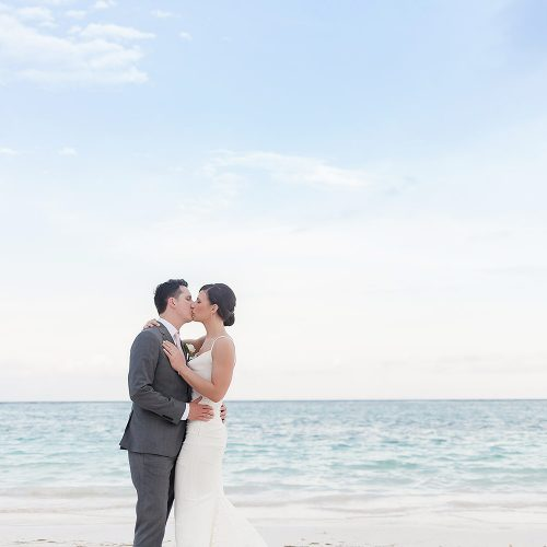Bride and groom kissing on beach at Secrets Akumal Riviera Maya