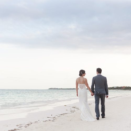 Bride and groom walking on beach at Secrets Akumal Riviera Maya