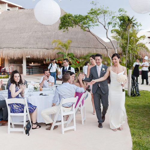 Bride and groom showing up to poolside reception at Secrets Akumal Riviera Maya wedding