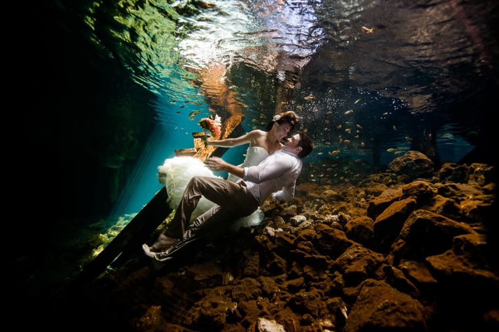 Bride and groom laying down underwater in Mayan Cenote Trash the Dress