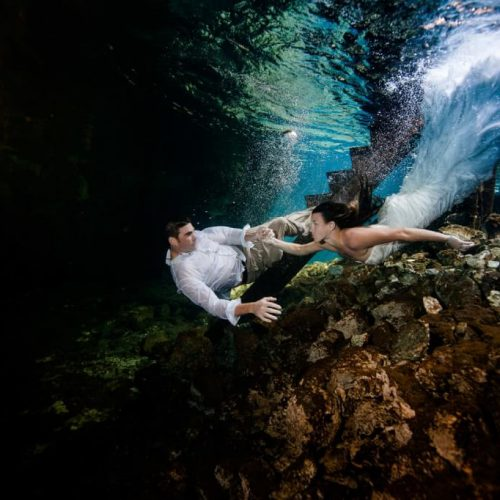 Bride and groom swimming under water in mayan cenote Trash the Dress.
