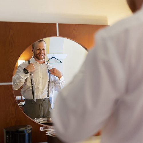 Groom looking in the mirror for his Playa del Carmen wedding