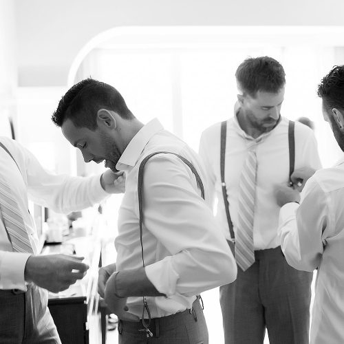 Black and white photo of groomsmen getting ready at Riviera Maya