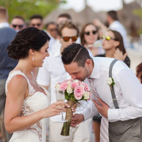 groom sniffing flowers bouquet at Playa del Carmen Wedding