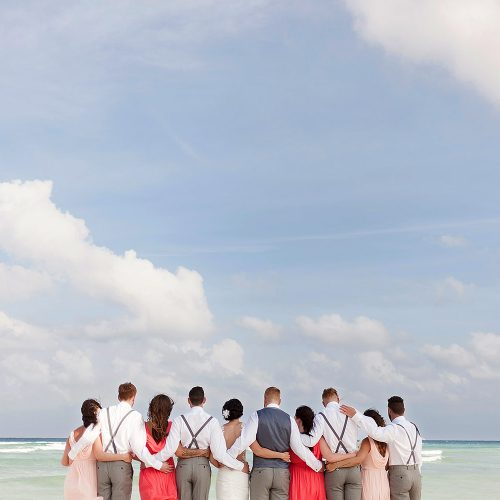 Bridal party on the beach looking at the ocean at Playa del Carmen wedding photography
