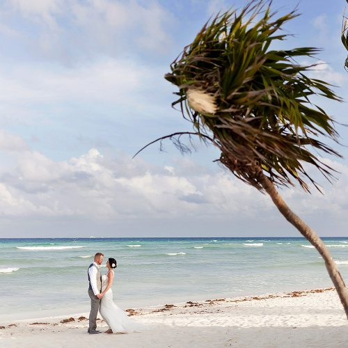 Bride and Groom on the beach with palm tree at Playa del Carmen beach wedding