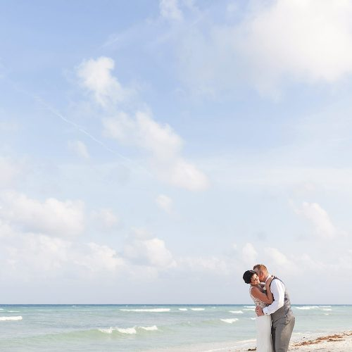 Bride and groom kissing on the beach at Riviera Maya