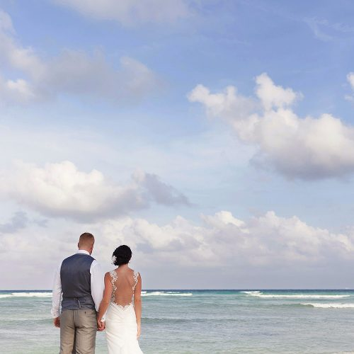 Bride and groom on the beach looking at the ocean at Playa del Carmen wedding