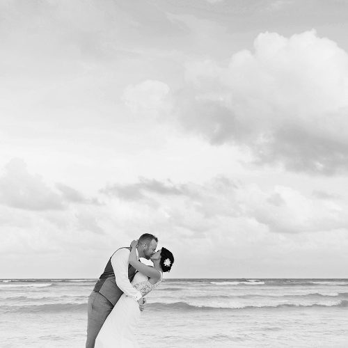 Black and white photography of bride and groom kissing on the beach at Playa del Carmen wedding