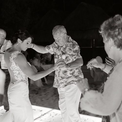 black and white photography of bride and father having fun at Playa del Carmen wedding reception