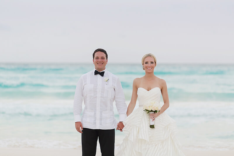 Bride and groom standing on beach in Canucn