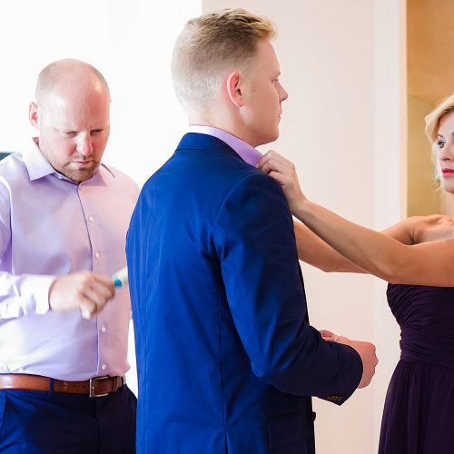 Bridesmaid helping groom before gay wedding