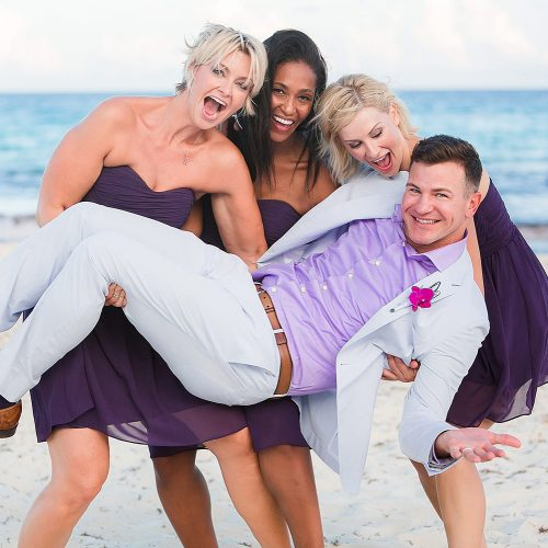Bridesmaids holding groom up at wedding.