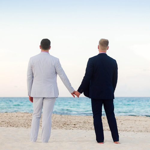 Grooms holding hands and looking out to sea at gay wedding in Cancun