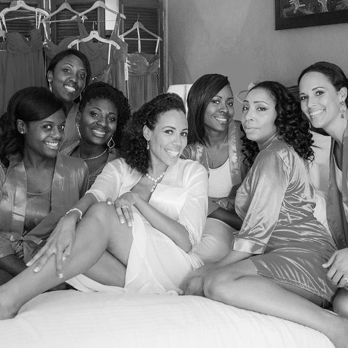 Bride and bridesmaids on bed at El Dorado Seaside Suites