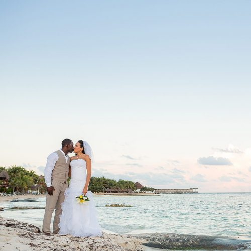Portrait of bride and groom on beach at El Dorado Seaside Suites