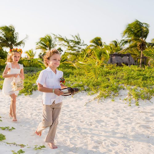 Flower girls and ring bearer walk down sand aisle in Tulum