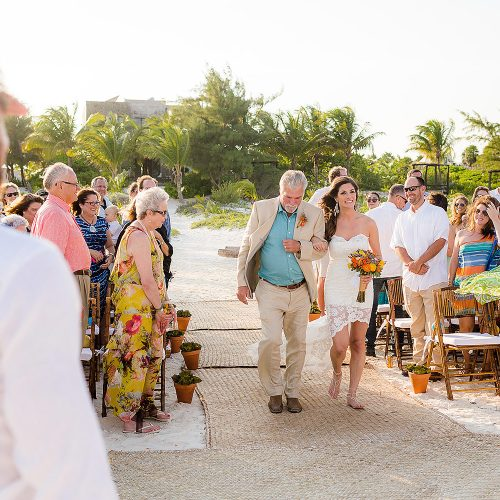 Bride and father walk down sand aisle at beach wedding in Tulum