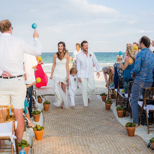 Bride and groom walk back down aisle after wedding in Tulum