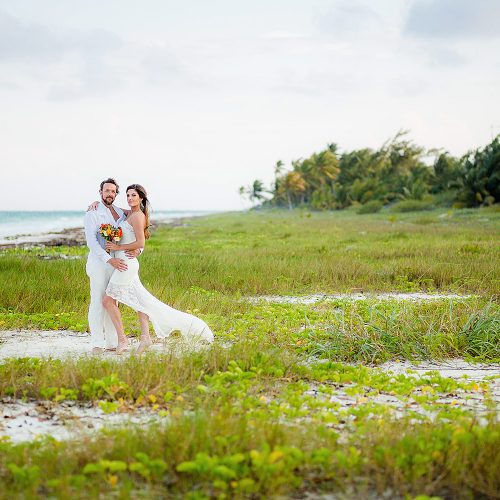 Portrait of Bride and groom in grass near beach after wedding in Tulum