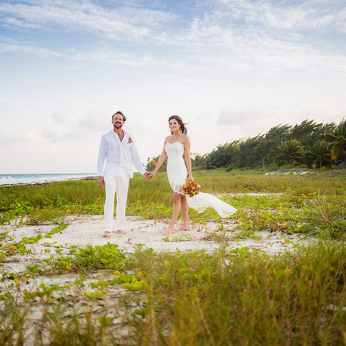 Portrait of Bride and groom in holding hands in grass near beach after wedding in Tulum