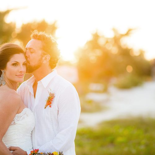 Groom kissing bride in beautiful sunset