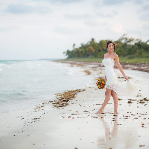 Bride on beach in Tulum after wedding.