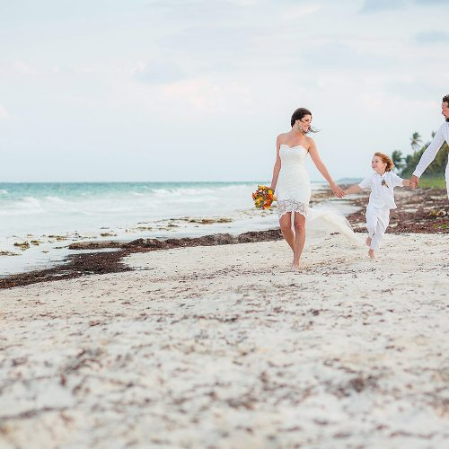 Bride and groom walking with son after wedding in Tulum