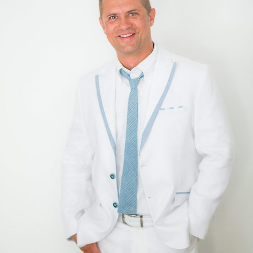 Portrait of groom before wedding wearing white suit