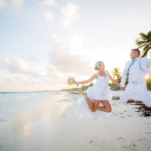 Bride and groom jumping on beach in Tulum