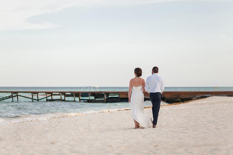 Bride and groom walking on beach in Riviera Maya