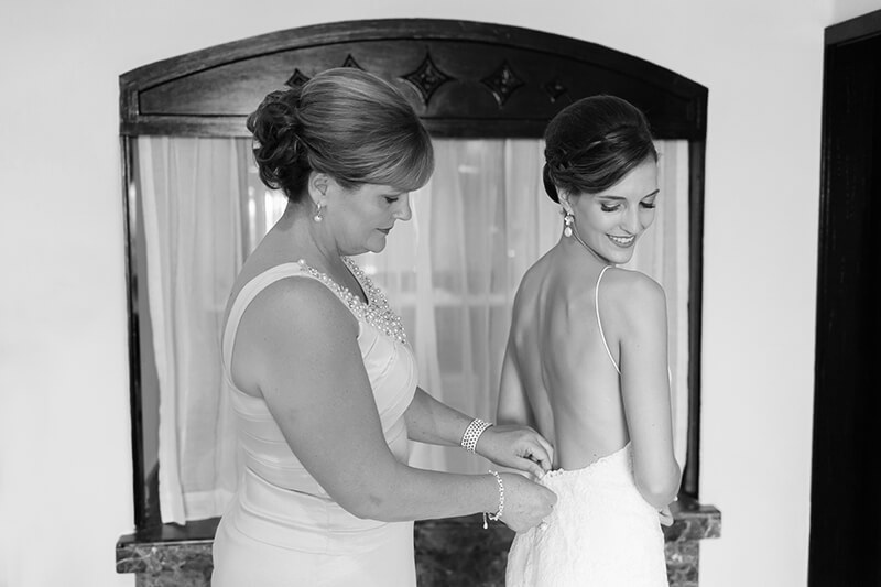 Mother putting on brides dress at Secrets Maroma Beach Riviera Cancun Resort