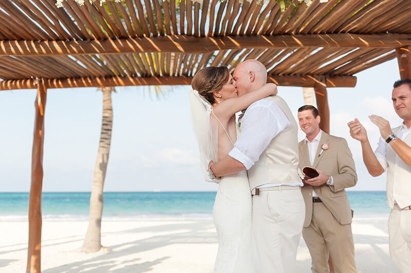 Bride and groom kissing after getting married at Secrets Maroma Beach Riviera Cancun Resort