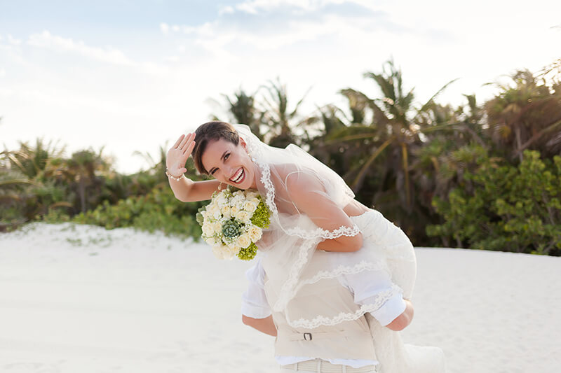 Groom carrying bride after wedding at Secrets Maroma Beach wedding