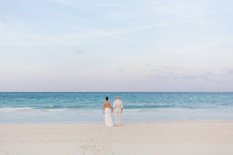 Bride and groom looking at the ocean at Secrets Maroma Beach