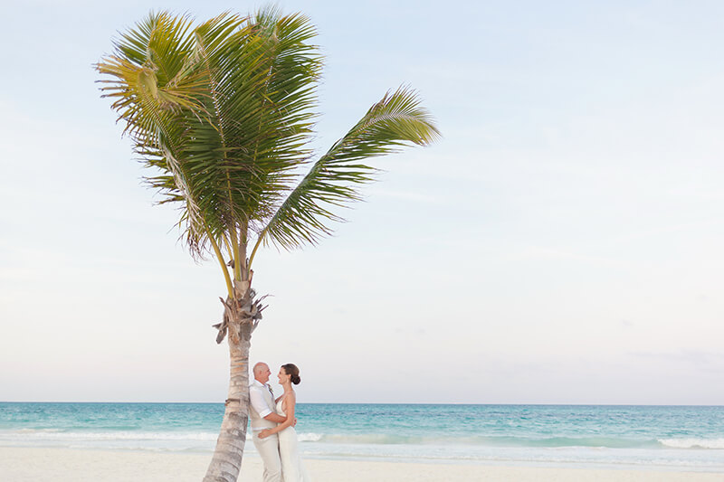Couple portrait at the beach with a palm tree at Secrets Maroma Beach wedding
