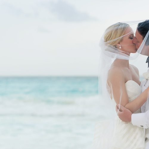 Couple under veil kissing a Hard Rock Cancun beach wedding