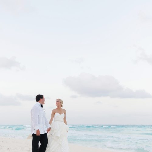 groom and bride walking on the beach at Hard Rock Cancun
