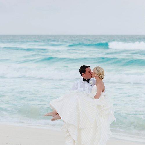 Groom carrying bride at Hard Rock Cancun beach wedding