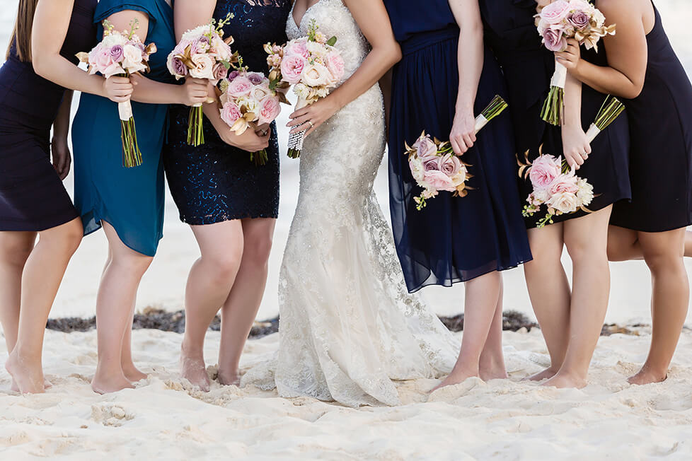 Close up of bridesmaids and flowers on beach in Cancun