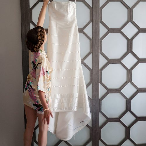 Bride reaching for dress at Azul Fives Hotel, Riviera Maya