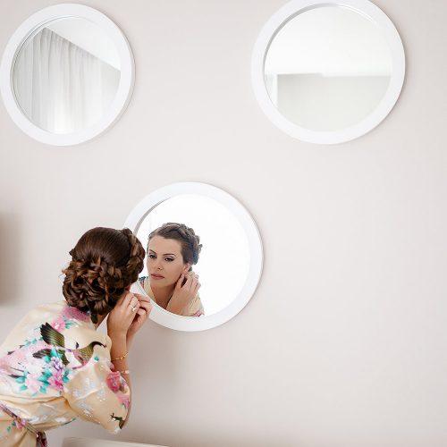 Bride looking in mirror getting ready at Azul Fives Hotel, Riviera Maya