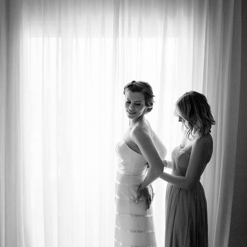 Bride and bridesmaid putting on dress at Azul Fives Hotel, Riviera Maya
